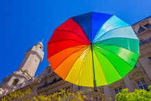 Multicolored Umbrella Flying In A City