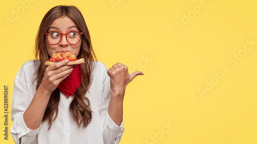 Photo of attractive woman eats slice of pizza, points aside with thumb, dressed in fashionable clothes, shows where pizzeria is, isolated over yellow background Fototapete