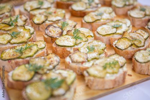 Catering / Belegte Brote mit Zucchini und Käse überbacken auf Holzbrett