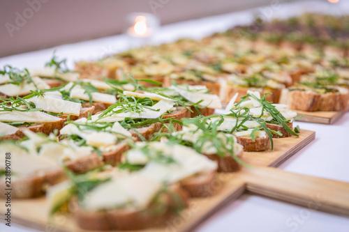 Foto op Plexiglas Buffet, Bar Catering / Belegte Brote mit Käse und Ruccola auf Holzbrett