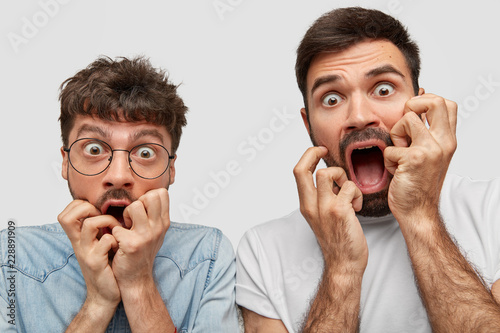 Close up shot of emotive stupefied men stare at camera with bugged eyes full of fear, keep hands near opened mouthes, stand closely to each other, isolated over white background. Shock concept