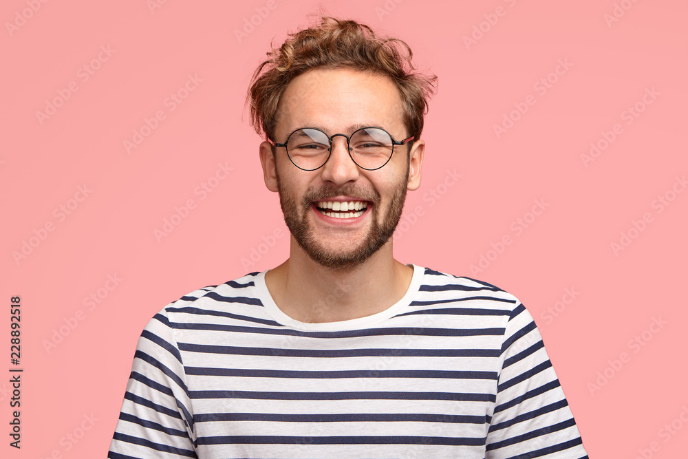 Fototapeta Headshot of pleased hipster has satisfied expression, curly hair and bristle, wears round transparent glasses and striped t shirt, feels glad after promotion at work, isolated over pink background