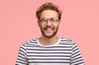 canvas print picture - Headshot of pleased hipster has satisfied expression, curly hair and bristle, wears round transparent glasses and striped t shirt, feels glad after promotion at work, isolated over pink background