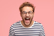 Leinwanddruck Bild - Crazy man yells loudly, has overjoyed facial expression, shouts for his favourite team, wears round transparent glasses and striped clothes, poses over pink background. Amazed hipster exclaims