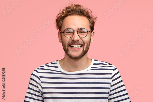 Fotografía  Headshot of pleased hipster has satisfied expression, curly hair and bristle, we