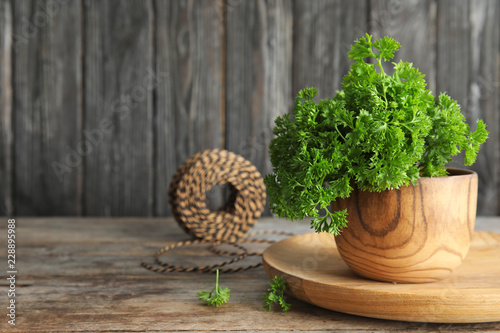 Bowl with fresh green parsley on wooden table. Space for text