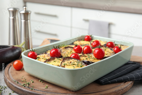 Baked eggplant with tomatoes and cheese in dishware on table against blurred background