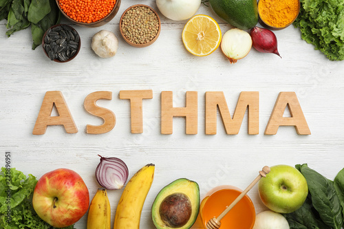 Flat lay composition with natural products as home remedies and word ASTHMA on wooden background
