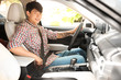 Male driver fastening safety belt in car