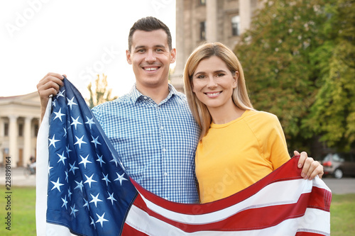 Couple with American flag on city street
