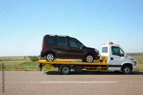 Tow truck with broken car on country road Wallpaper Mural