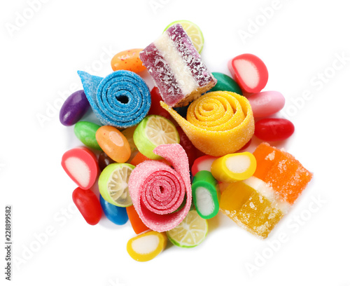 Pile of delicious colorful chewing candies on white background, top view