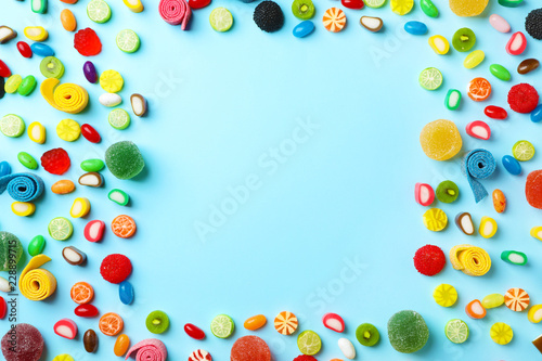 Flat lay composition with delicious colorful candies and space for text on color background
