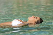 Relaxed Woman Floating In A Tropical Beach Water