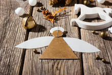 Handmade Paper Angel And Other Christmas Ornaments On Weathered Old Wooden Table, With Shades