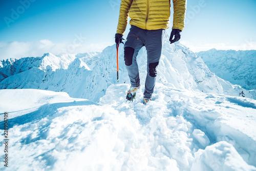 In de dag Alpinisme A climber ascending a mountain in winter