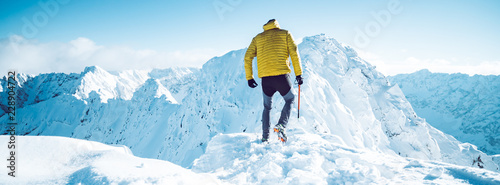 Deurstickers Alpinisme A climber ascending a mountain in winter