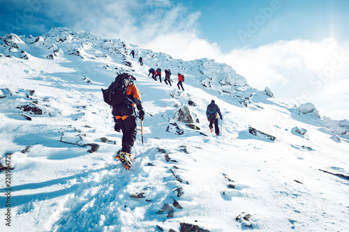 Deurstickers Alpinisme A group of climbers ascending a mountain in winter