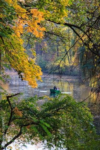 Romantic scene in the autumn park. The couple in the boat.