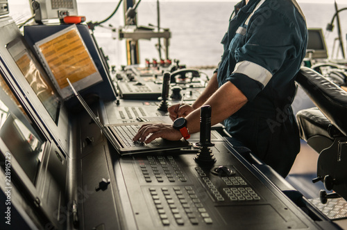 Valokuva  Marine navigational officer or technician is using laptop or notebook at sea