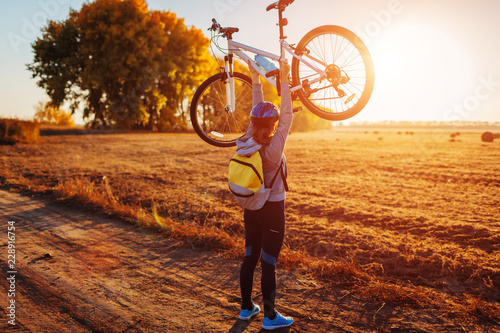 Young bicyclist raising her bicycle in autumn field. Happy woman celebrates victory holding bike in hands
