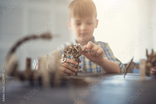 Fotografie, Tablou  Concentrated kid sitting at the table and looking concentrated while creating un
