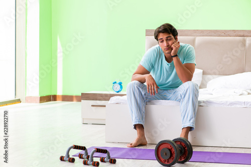 Photo Young man in pajamas doing morning exercises