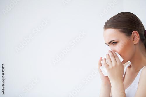 Valokuva  Sick woman using paper tissue, headcold problem
