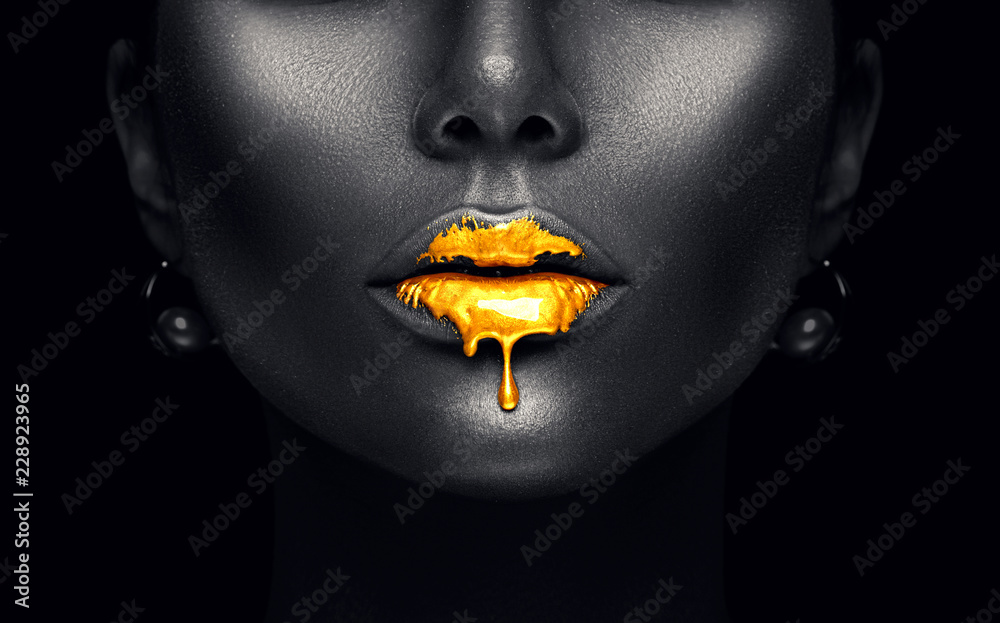 Fototapeta Gold paint drips from the sexy lips, golden liquid drops on beautiful model girl's mouth, creative abstract dark black skin makeup. Beauty woman face isolated on black