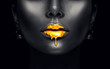 Gold paint drips from the sexy lips, golden liquid drops on beautiful model girl's mouth, creative abstract makeup. Beauty woman face isolated on black