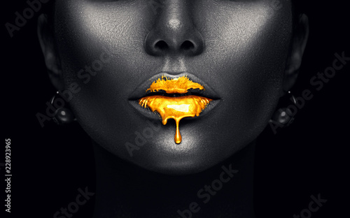 Gold paint drips from the sexy lips, golden liquid drops on beautiful model girl's mouth, creative abstract dark black skin makeup. Beauty woman face isolated on black