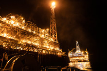 FPSO Tanker Vessel Near Oil Platform Rig. Offshore Oil And Gas Industry, Sea Oil Production And Storage. Flare Boom Is Brightly Burning At Night.
