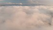 Flying over the clouds at dusk or at dawn. Flying above the clouds in the direction of a high snowy mountain. Aerial view. North Caucasus