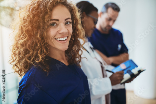 Smiling young medical intern standing with doctors in a hospital