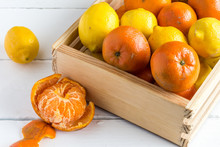 Rustic Crate With Whole Fruit Lemons And Clementines On White Table