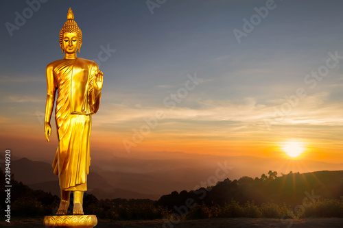 Golden Buddha statue on sunrise background