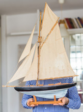 Hobby, Interior And Collecting Concept - Handsome Man Holding The Layout Of A Sailboat In The Room