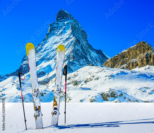 Ski in winter season, mountains and ski touring backcountry equipments on the top of snowy mountains in sunny day with Matterhorn in background, Zermatt in Swiss Alps.