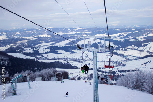 Fotografie, Obraz  Cable car with skiers in the mountains, winter holidays, Ukrainian Carpathians,