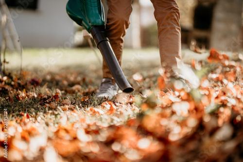 Gardener using leaf blower, vacuum and working in garden Canvas Print