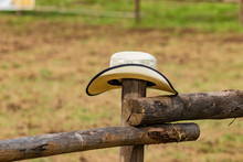 Western American White Cowboy Hat, Left On Wooden Fence, In Sign Of Surrender And Defeat. Italian Horses And Rodeo Show, Role Playing On Sunny, Summer Day. Equestrian Sports.