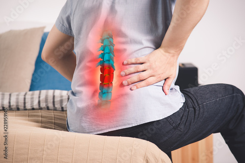Obraz na plátne Pain in the spine, a man with backache at home, injury in the lower back