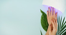 Beautiful Female Manicured Hands Andled Lamp On Blue Table
