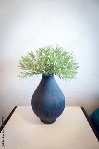 The long vertical blue vase is used to decorate the room. Canvas Print