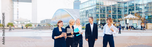 Fotografía  Members of business organization talking outside and smiling with document case and tablet in hands