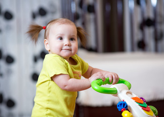 Fototapeta First steps of little child girl in baby walker