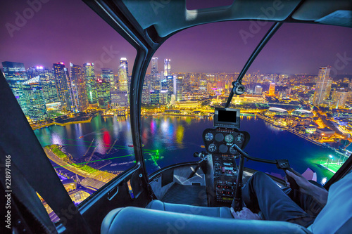 Scenic helicopter flight above Singapore skyline at dawn. Night urban aerial scene. cockpit interior with financial district skyscrapers at night on Singapore harbor.