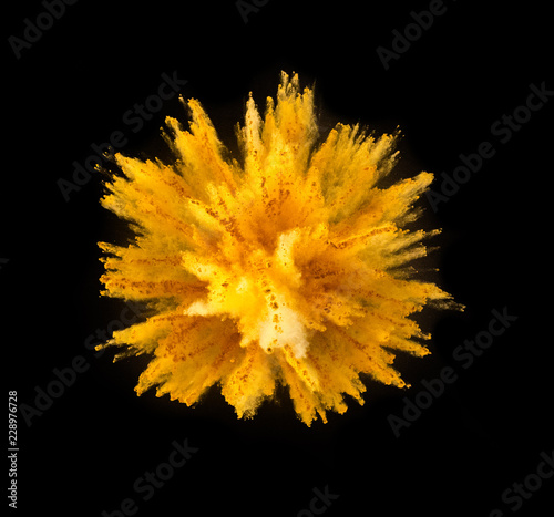 Explosion of yellow powder on black background