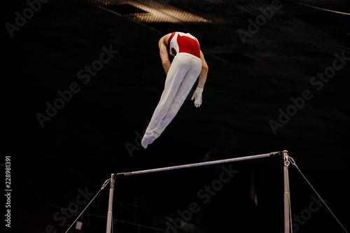 Spoed Fotobehang Gymnastiek gymnast exercise on high bar in artistic gymnastics