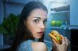 Hungry woman eating burger at night near fridge